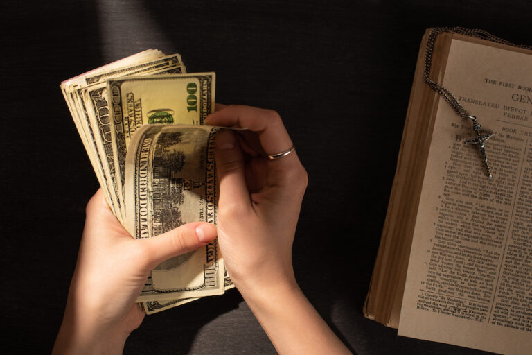 cropped view of woman counting money near holy bible with cross on dark background with sunlight